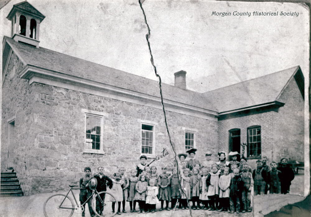 Single-story, stone building with belfry; women and children pose in front of the building