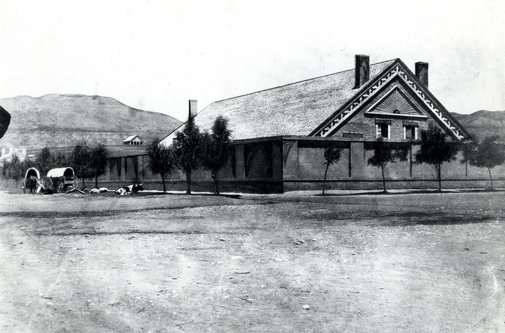 One-story adobe building surrounded by an adobe fence