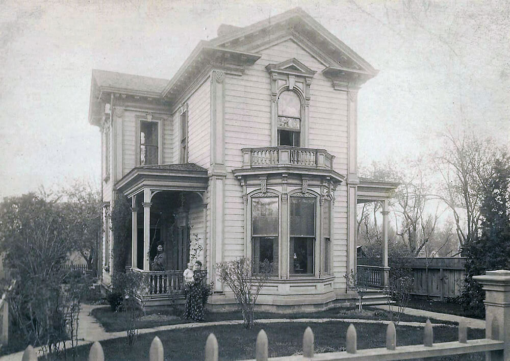 Two-story, wood home with front balcony and covered side porch; one woman stands on the porch while another holds a baby in the yard