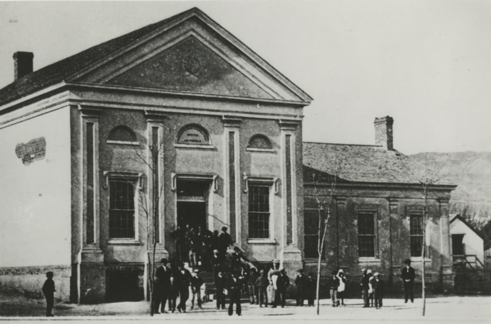 Large meetinghouse with a group of people entering, Salt Lake City Thirteenth Ward, circa 1890