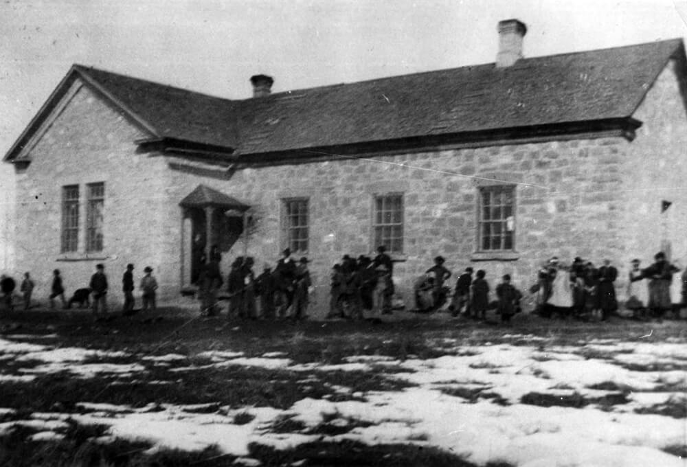 Single-story, rock schoolhouse with children playing outside