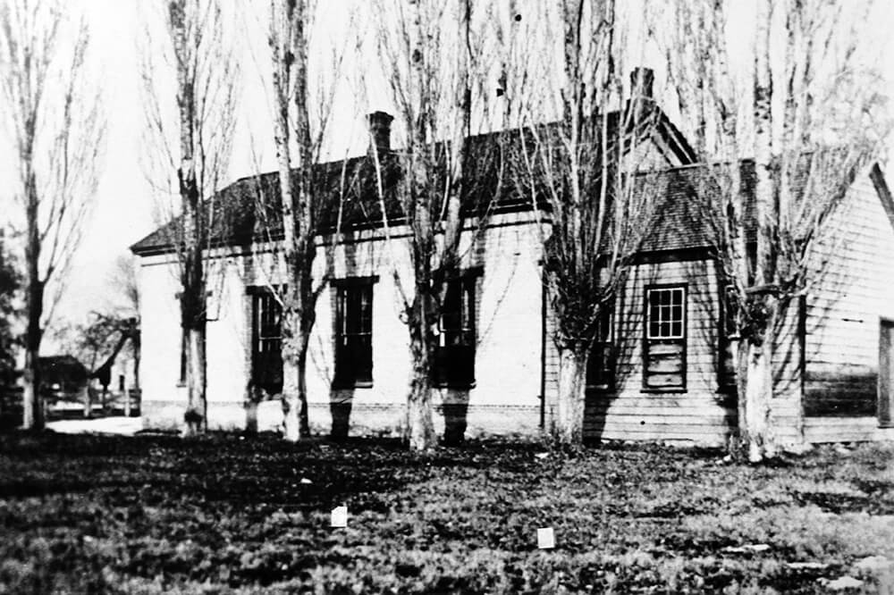 Single-story, wood home with rectangular windows and chimney