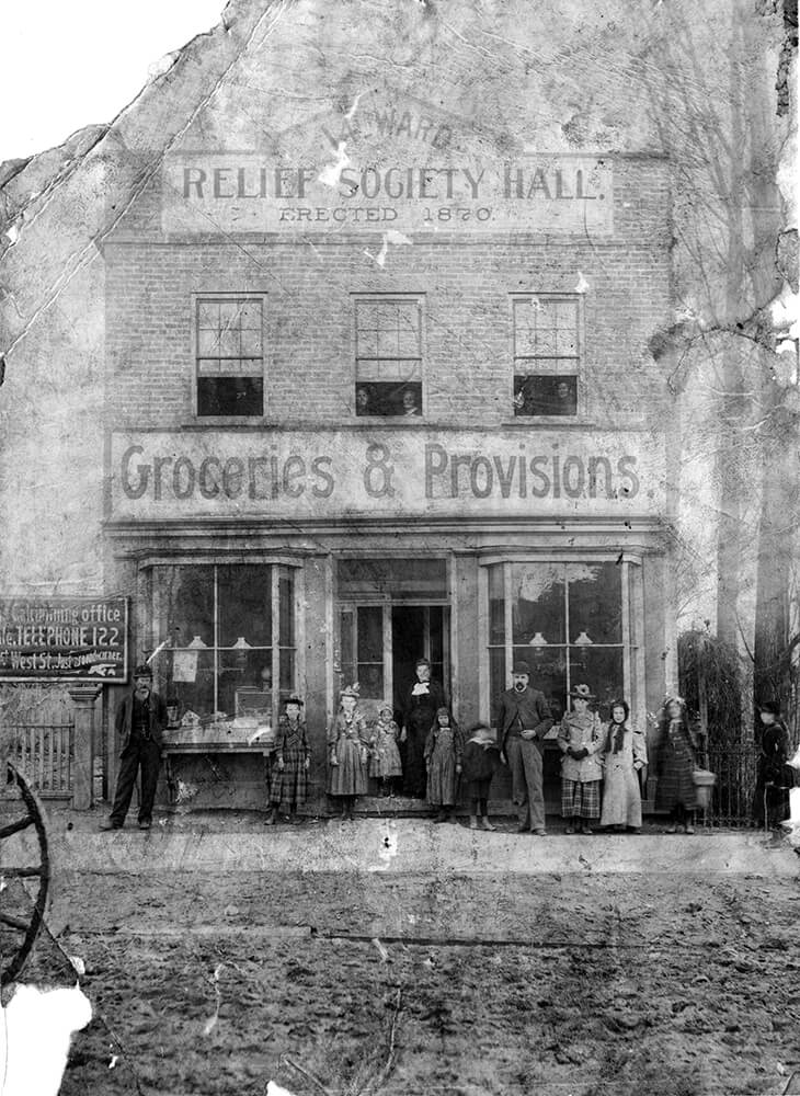 "Two-story, brick building surrounded by women, men and children and a sign above the entrance reading ""Groceries & Provisions"""