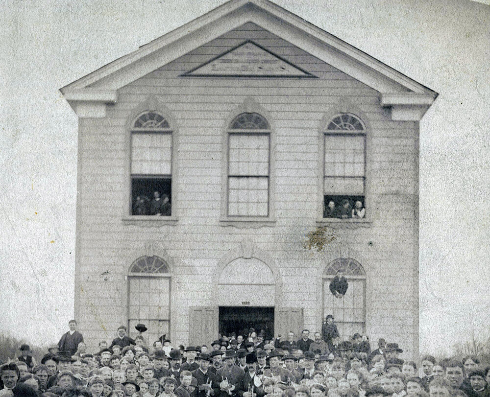 Two-story, brick building surrounded by women and men