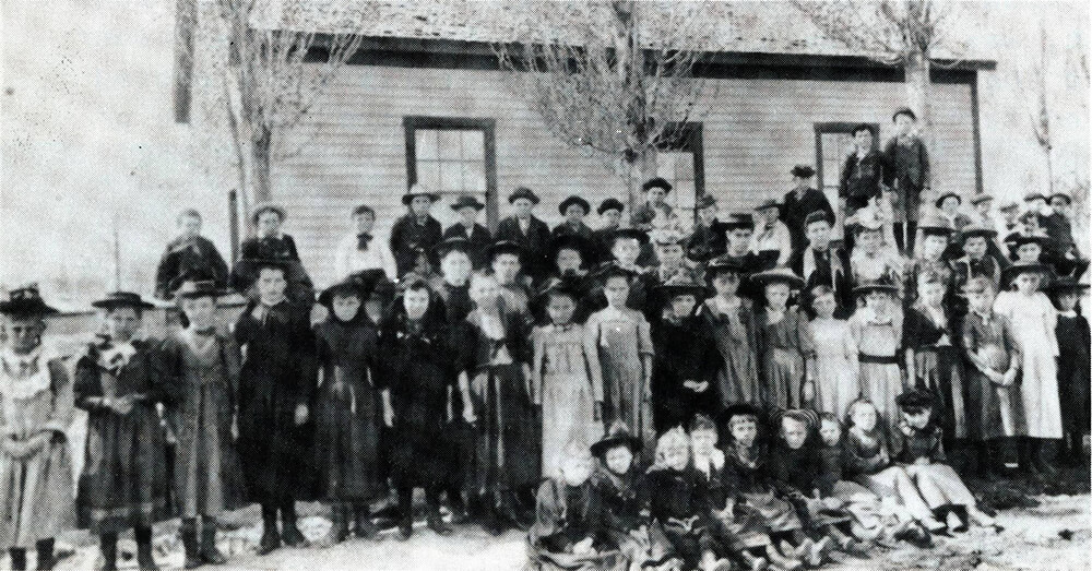 Large group of children pose in front of a one-story, one-room frame schoolhouse