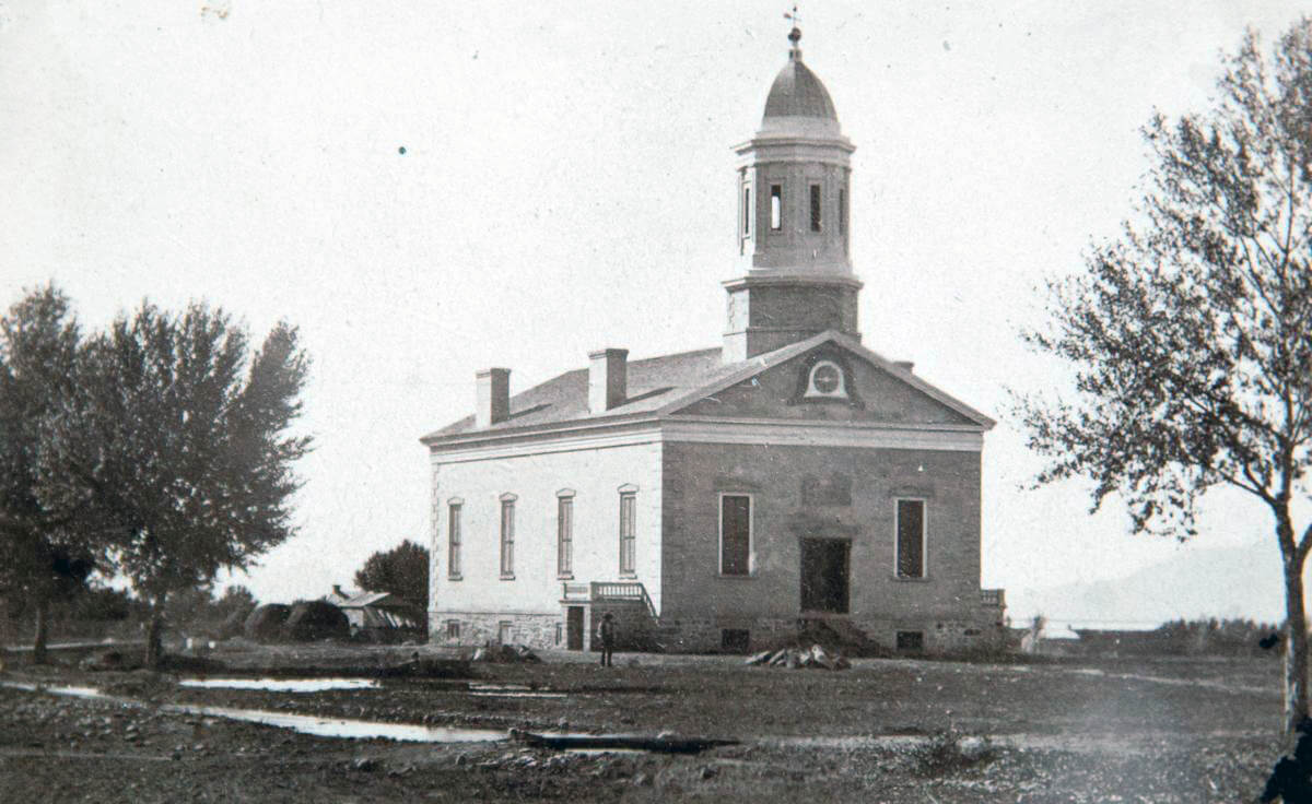 One-story, brick building with two chimneys and a steeple that includes a belfry