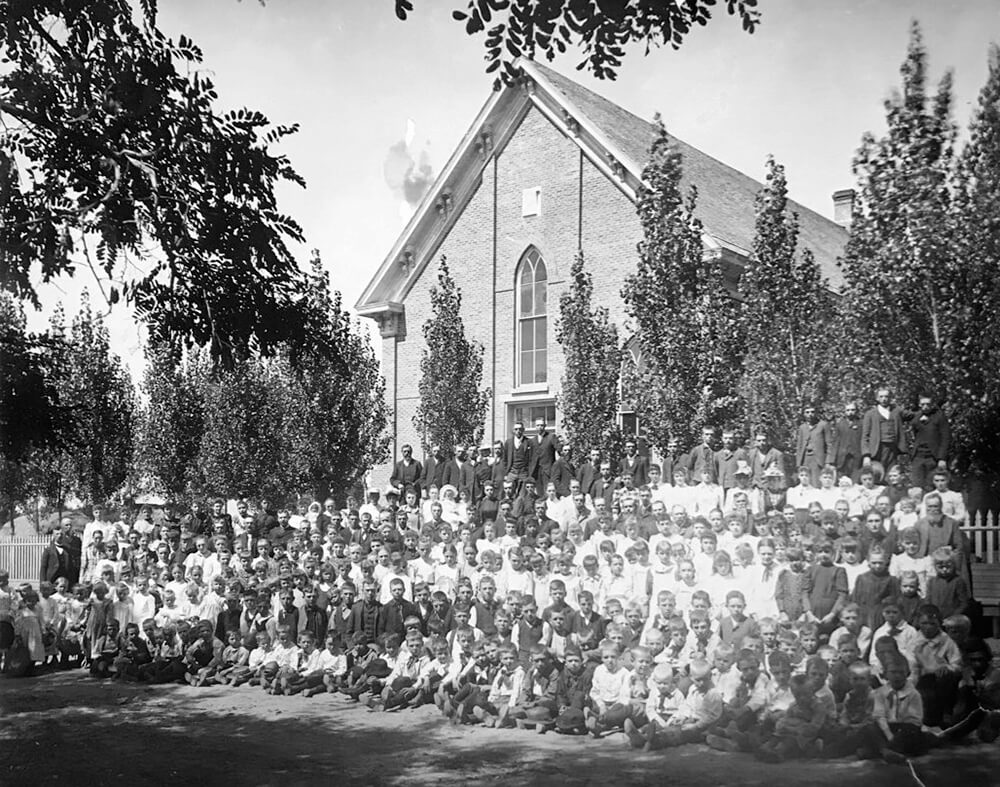 Large group of women, men, and children stand outside a large brick meetinghouse
