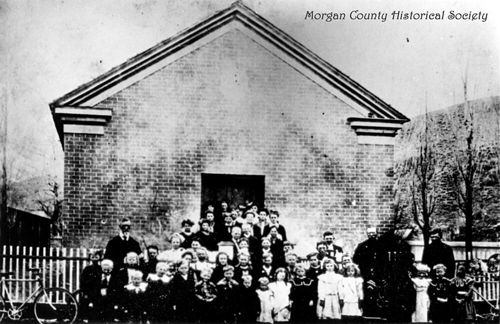 Single-story, brick building with children, men, and women congregated at the entrance