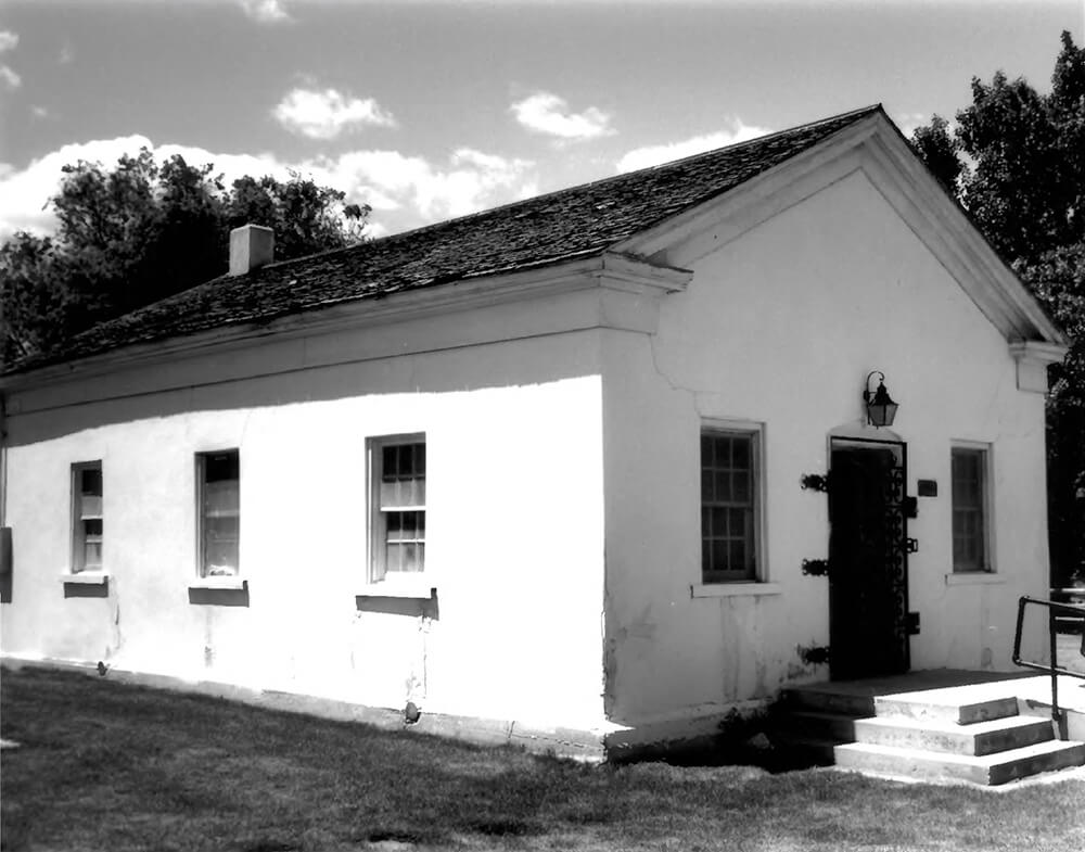 Single-story, white adobe building
