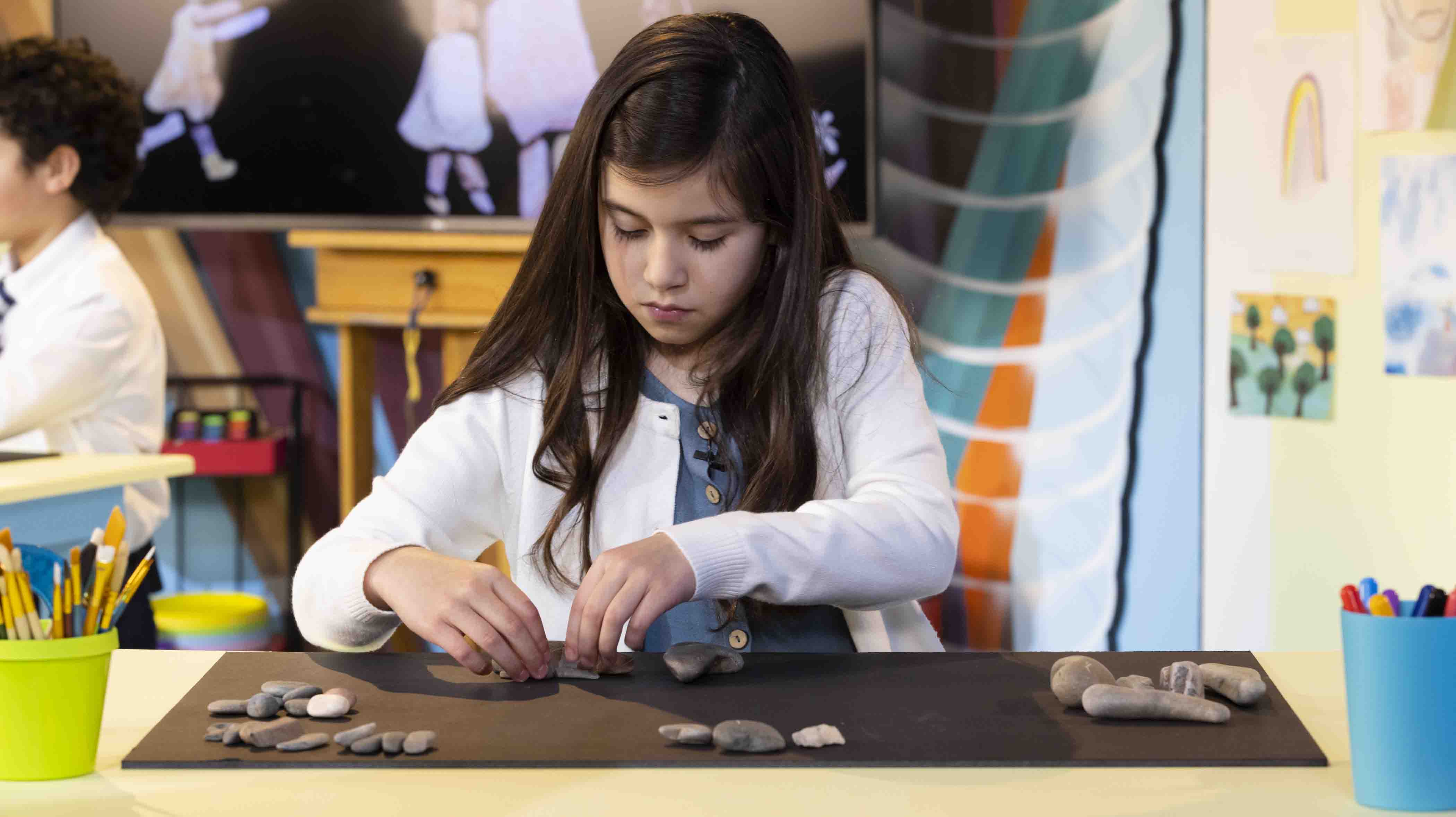 Girl making pictures with rocks