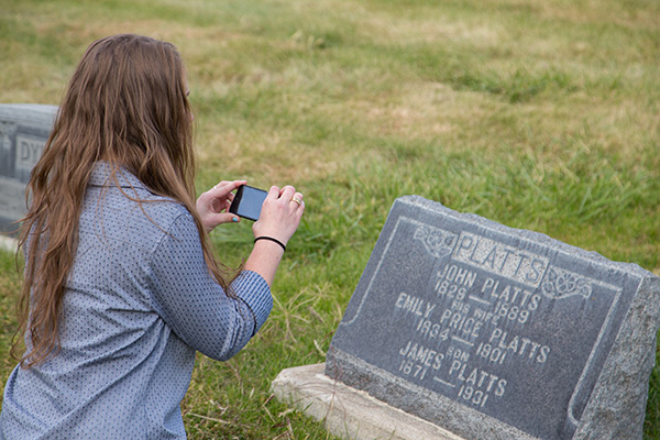 Girl taking a picture of a grave
