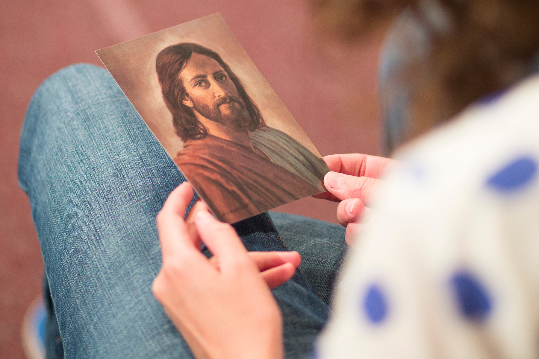 young woman looking at picture of Christ