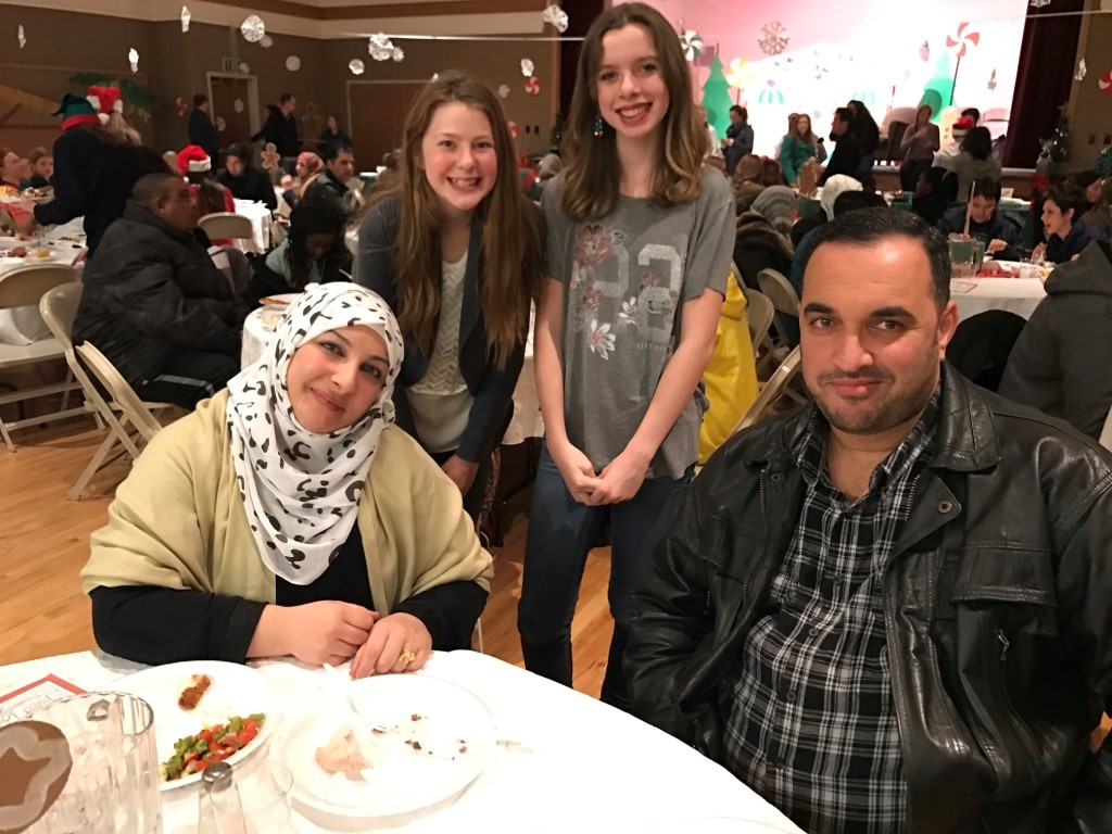Two girls welcome a refugee couple at a Christmas party.