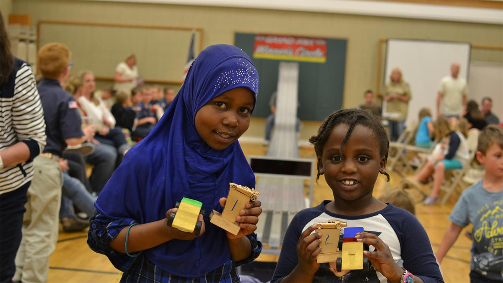 Two refugee girls with pinewood derby cars and trophies.