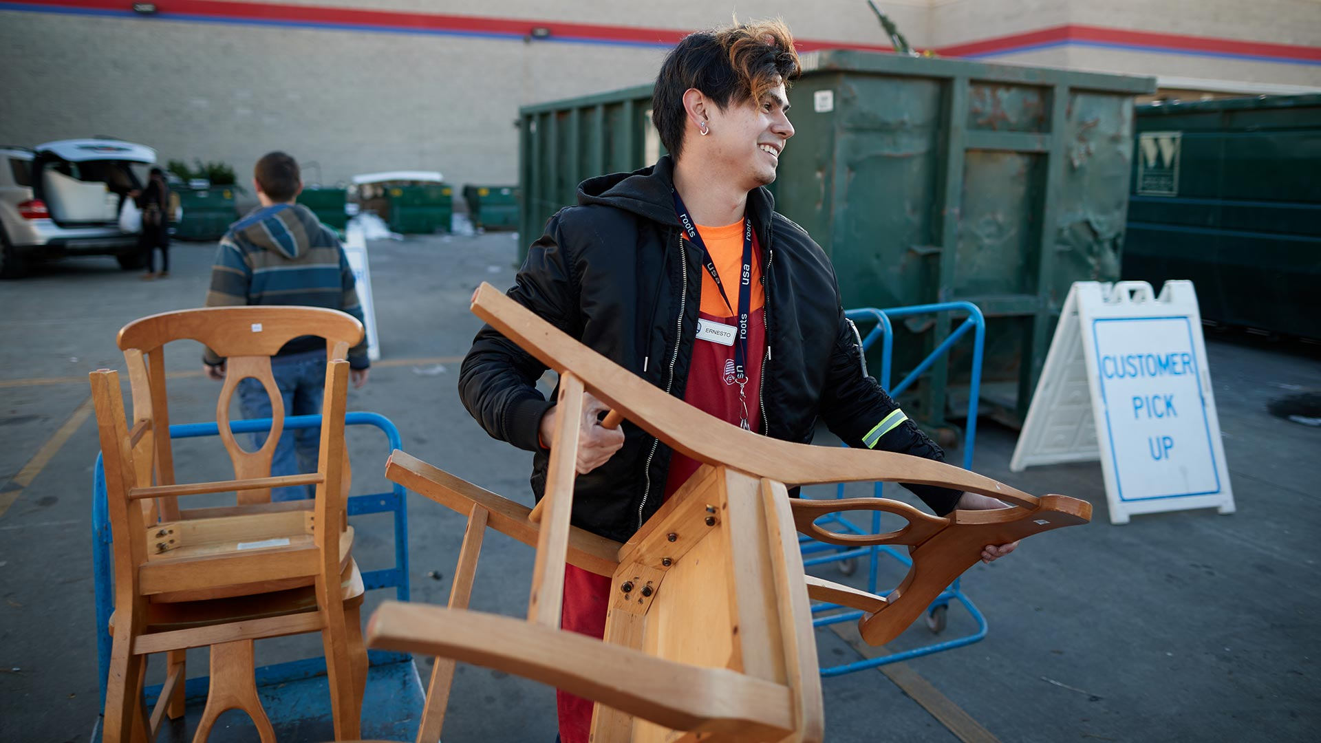 Associate Ernesto helps a customer pick up a donated chair
