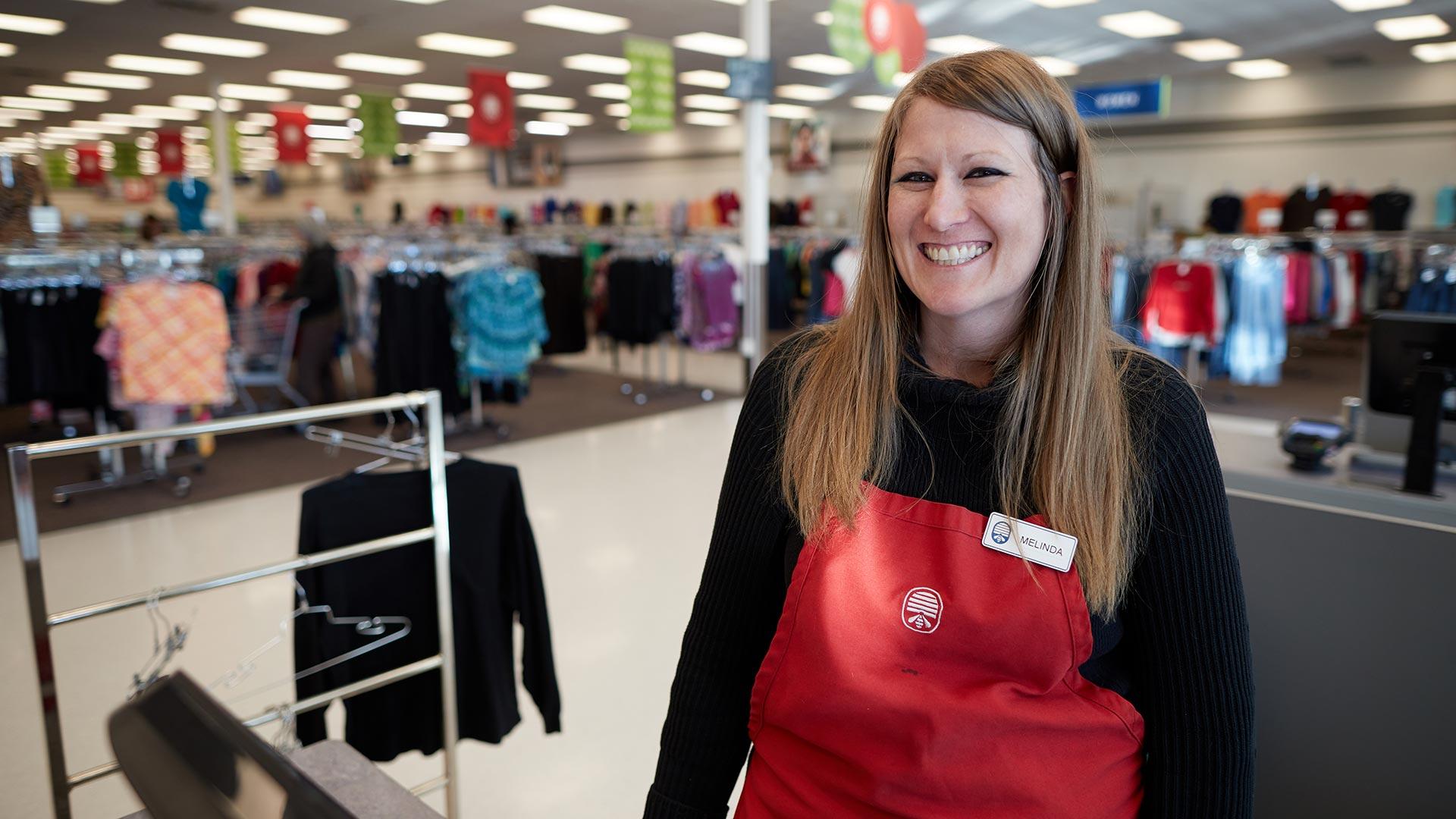 Associate Melinda smiles at a cash register at DI