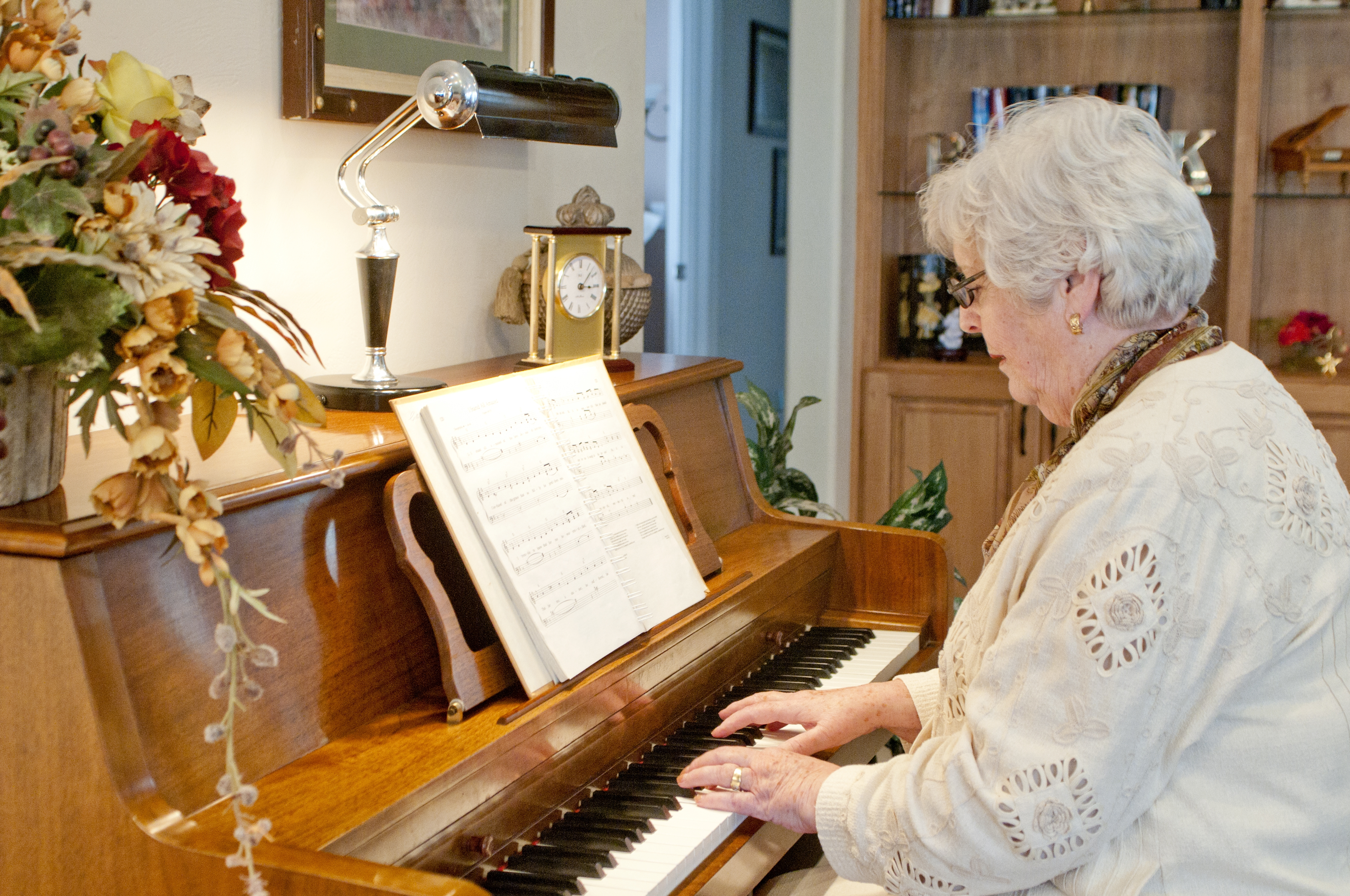 An older woman plays the piano