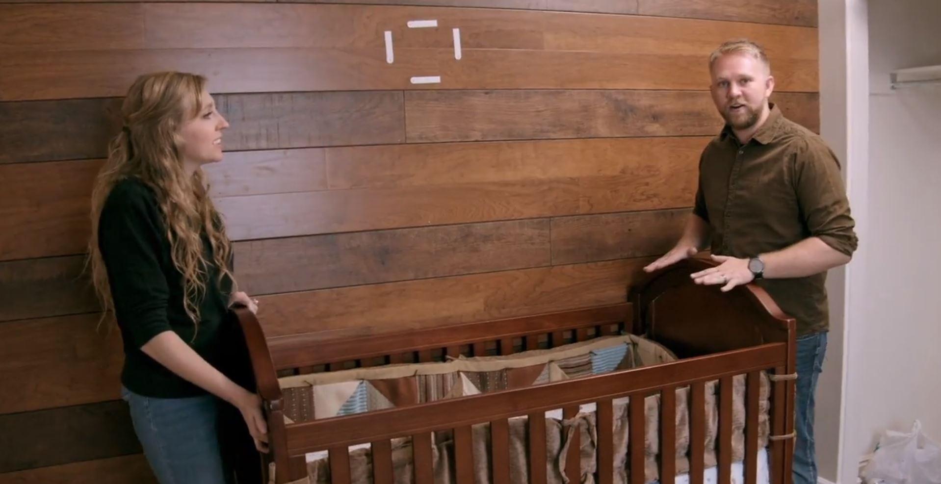 Celeste and Brixton move a crib.